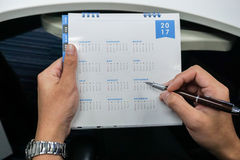 L'homme d'affaires arrangent rencontrer le 2017 le calendrier dans des mains Photos stock