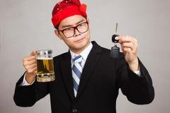 L'homme d'affaires asiatique avec le chapeau de partie décident la boisson ou conduisent Photos stock