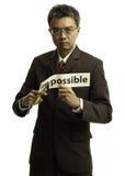 L'homme d'affaires asiatique a coupé le papier pour le mot possible Photo libre de droits