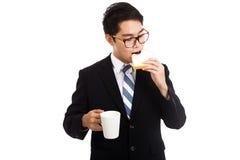 L'homme d'affaires asiatique mangent du pain et du café comme petit déjeuner Image stock