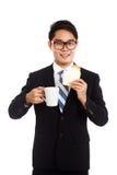 L'homme d'affaires asiatique mangent du pain et du café comme petit déjeuner Image libre de droits