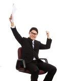 L'homme d'affaires asiatique s'asseyent sur la chaise de bureau heureuse avec le succès avec Photographie stock