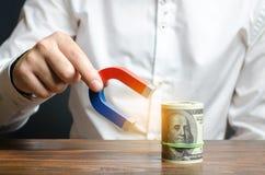 L'homme d'affaires attire l'argent avec un aimant Attirant l'argent et les investissements à des fins commerciales et les démarra images libres de droits
