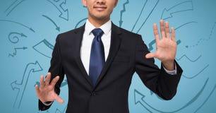 L'homme d'affaires avec distribue sur le fond bleu avec des graphiques de flèche photographie stock