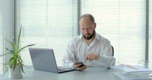 L'homme d'affaires avec l'ordinateur portable utilise le smartphone dans le bureau 4K clips vidéos