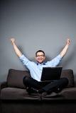 L'homme d'affaires avec l'ordinateur portatif soulève des bras Images stock