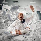L'homme d'affaires avec la bouée de sauvetage descend entre les fiches de travail dans le bureau photo libre de droits