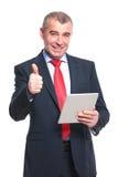 L'homme d'affaires avec le comprimé montre le pouce  Photo libre de droits