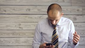 L'homme d'affaires avec le smartphone apprécie la mauvaise nouvelle banque de vidéos