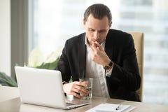 L'homme d'affaires avec le verre de l'eau prend autour de la pilule Image stock