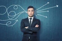 L'homme d'affaires avec les bras pliés se tenant près du mur bleu et des flèches tirées passe par sa tête Photographie stock libre de droits