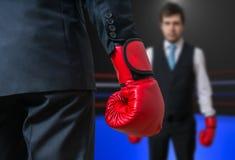 L'homme d'affaires avec les gants de boxe rouges enferme dans une boîte en anneau avec son patron Images libres de droits