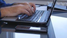 L'homme d'affaires avec un ordinateur portable dans le bureau intérieur saisissent des données utilisant le clavier numérique image stock