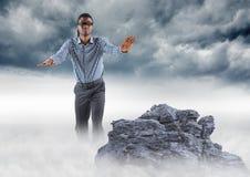L'homme d'affaires a bandé les yeux sur la crête de montagne brumeuse contre des nuages de tempête Photo stock