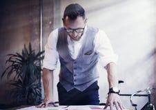 L'homme d'affaires barbu Analyzes Business Plan documente le lieu de travail moderne Jeune homme travaillant le Tableau de démarr photos libres de droits