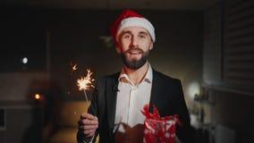 L'homme d'affaires barbu avec les étincelles et le chapeau du père noël parle la bonne année de souhaits et regarde la caméra ave banque de vidéos