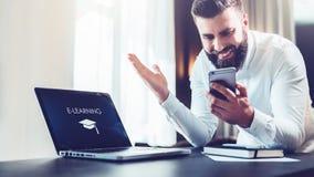 L'homme d'affaires barbu dans une chemise blanche s'assied à une table devant un ordinateur portable avec un apprentissage en lig image stock