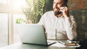 L'homme d'affaires barbu de sourire de jeunes s'assied à la table devant l'ordinateur portable, café potable, parlant au téléphon images stock