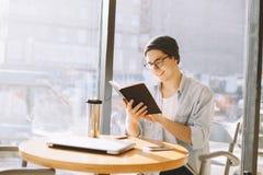 L'homme d'affaires bel dans la tenue de détente et des lunettes utilise un ordinateur portable en café photographie stock