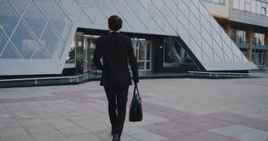 L'homme d'affaires bel vient au travail le matin tenant sa serviette banque de vidéos