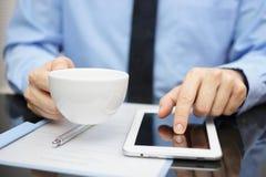 L'homme d'affaires boit du café et travaille sur la tablette Images stock