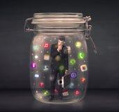 L'homme d'affaires a capturé dans un pot en verre avec l'escroquerie colorée d'icônes d'APP Image libre de droits