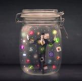 L'homme d'affaires a capturé dans un pot en verre avec l'escroquerie colorée d'icônes d'APP Photos stock
