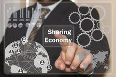 L'homme d'affaires clique sur dessus l'économie partageante sur l'éboulis de contact photo stock