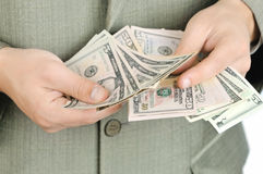 L'homme d'affaires compte l'argent dans des mains. Photo stock