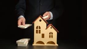L'homme d'affaires compte un argent et le jette sur une table près du modèle de maison photographie stock