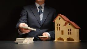 L'homme d'affaires compte une pile d'argent près d'un modèle de maison sur une table photographie stock
