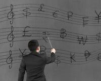 L'homme d'affaires conduisant avec des symboles d'argent stave sur le mur Images libres de droits
