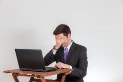 L'homme d'affaires couvre ses yeux devant un ordinateur portable Photos stock