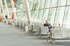 L'homme d'affaires d'aéroport avec le téléphone intelligent attend dans le terminal Photographie stock