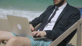L'homme d'affaires dactylographie l'email d'affaires sur la plage clips vidéos