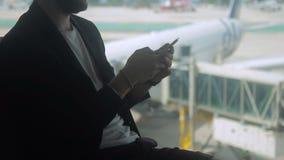 L'homme d'affaires dactylographie le texte sur l'écran de son smartphone dans l'aéroport clips vidéos