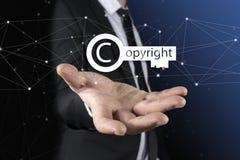 L'homme d'affaires dans des ses mains garantissent les droits d'auteur l'icône principale au-dessus de la tache floue colorée, du photos stock
