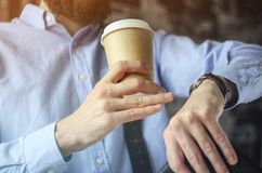 L'homme d'affaires dans la chemise bleue boit du café et regarde sa montre quittant le bureau Concept de pause-café photo stock