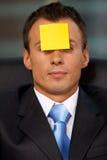 L'homme d'affaires dans le bureau avec la note adhésive vide a collé au front images stock