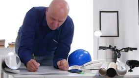L'homme d'affaires dans le bureau de société écrivent la documentation technique et effectuent le calcul banque de vidéos