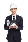 L'homme d'affaires dans le casque remet la maison et la disposition modèles Photos stock