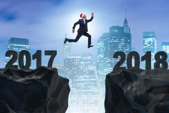 L'homme d'affaires dans le chapeau de Santa sautant à partir de 2017 à 2018 Photographie stock libre de droits