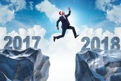 L'homme d'affaires dans le chapeau de Santa sautant à partir de 2017 à 2018 Image stock