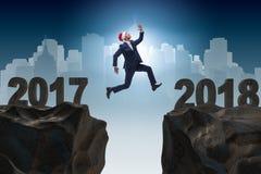 L'homme d'affaires dans le chapeau de Santa sautant à partir de 2017 à 2018 Photographie stock