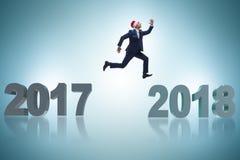 L'homme d'affaires dans le chapeau de Santa sautant à partir de 2017 à 2018 Images stock