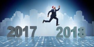 L'homme d'affaires dans le chapeau de Santa sautant à partir de 2017 à 2018 Photos stock