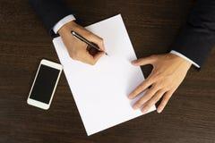 L'homme d'affaires dans le costume écrit sur la feuille blanche de vue supérieure de papier Bureau de travail d'un employé de bur image libre de droits