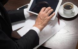 L'homme d'affaires dans le costume utilise le comprimé sur le café de tasse de table, mobile, stylo Photo stock