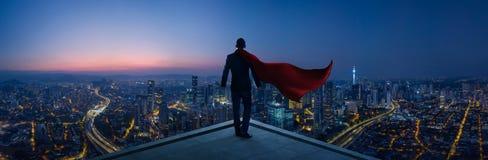L'homme d'affaires dans le héros de costume et de cap se tiennent au dessus de toit semblant le grand paysage urbain photographie stock libre de droits
