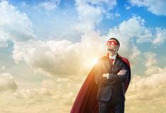 L'homme d'affaires dans un cap rouge et un masque d'oeil rouge se tenant avec des mains a croisé sur le fond opacifié de ciel Images stock